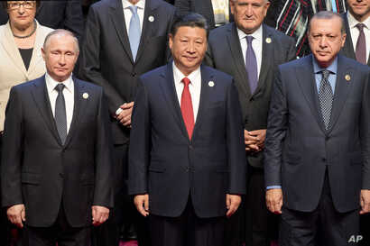 Chinese President Xi Jinping (center) stands with Russian President Vladimir Putin (left) Turkish President Recep Tayyip Erdogan (right) and other leaders to pose for a group photo before the opening ceremony of the Belt and Road Forum the China Nati...