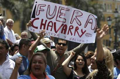 """A demonstrator holds up a poster that reads in Spanish: """"Get out Chavarry!"""", referring to Attorney General Pedro Chavarry, in Lima, Peru, Jan. 2, 2019."""