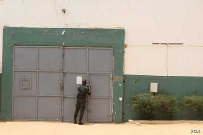 A guard bolts the door of the Thies detention centre, one of Senegal's 38 prisons, where almost 30 percent of female convicts are charged with infanticide. Thies, Senegal, June 1, 2018. (S. Christensen for VOA)
