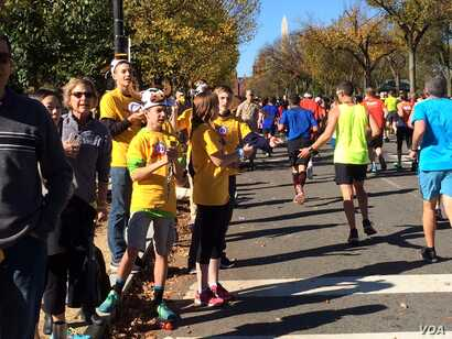 Teens wearing cow-horn hats and ringing cow bells cheer on runners in the Marine Corps Marathon along Independence Avenue Sunday.