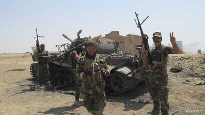 Iraqi Shiite militia fighters celebrate, near the wreckage of a tank belonging to Islamic State militants, after breaking a long siege of Amerli by Islamic State militants, September 2, 2014. Iraqi security forces backed by Shi'ite militias on Sunday