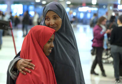 FILE  - Halima Mohamed embraces her daughter in New York, March 8, 2017. Mohamed and her husband, who are from Somalia but live in the U.S., originally expected their daughters to arrive earlier this year, but the process was delayed due to the initi...