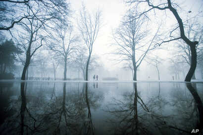 Strollers walk during morning fog at the City Park of Budapest, Hungary, Feb. 3, 2017.