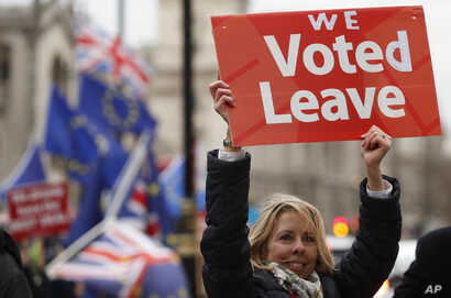 FILE - A pro-Brexit demonstrator waves a placard with others outside the Houses of Parliament in London, Britain, Dec. 18, 2018.