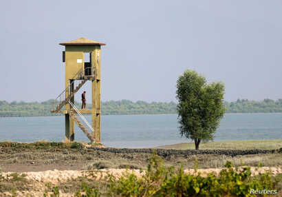A member of Border Guard Bangladesh (BGB) stands guard on a watchtower near the Bangladesh-Myanmar border to prevent Rohingya refugees from illegal border crossing, in Teknaf near Cox's Bazar, Bangladesh, Nov. 22, 2016.