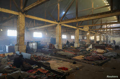 Migrants wrapped in blankets sleep on a floor inside a derelict customs warehouse in Belgrade, Serbia, Nov. 11, 2016.
