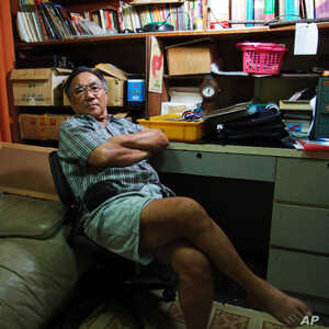 Hew Yun Tuck sitting in his office, where he kept extensive documentation of the rare earth mining controversy in Bukit Merah and Papan.