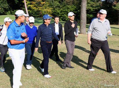 U.S. President Donald Trump (R) talks with Japan's PM Shinzo Abe as Japanese professional golfer Hideki Matsuyama looks on, as they play golf at the Kasumigaseki Country Club in Kawagoe, in this photo released by Japan's Cabinet Public Relations Offi...