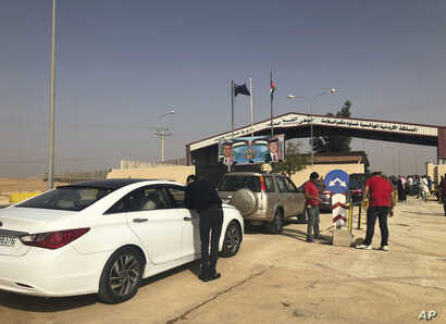 FILE - Jordanian cars prepare to cross into Syria, at the Jordanian-Syrian border Jaber crossing point, in Mafraq, Jordan, Oct. 15, 2018.