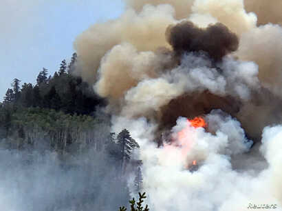 In this photo provided by Inciweb, flames and smoke billow skyward as a wildfire burns near Durango, Colo., June 7, 2018.