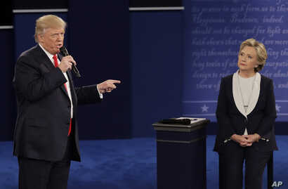 Republican presidential nominee Donald Trump speaks to Democratic presidential nominee Hillary Clinton during the second presidential debate at Washington University in St. Louis, Sunday, Oct. 9, 2016.