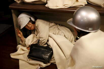 A woman takes shelter after another earthquake hit the area at a hotel in Kumamoto, southern Japan, in this photo taken by Kyodo, April 16, 2016.