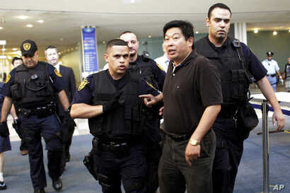 [÷/ُ - Dr. Yang Jianli, second from right,  president of Initiatives for China, is escorted by United Nations security after staging a demonstration inside the lobby of the United Nations headquarters, Tuesday, Aug. 31, 2010.
