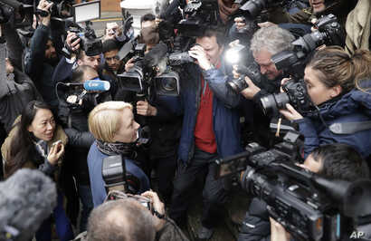 Swedish Chief Prosecutor Ingrid Isgren is surrounded by journalists as she arrives at the Ecuadorian embassy to interview Wikileaks founder Julian Assange in London, Nov. 14, 2016.