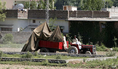 This May 2, 2011 file photo shows a tractor trolley carrying the wreckage of a helicopter that crashed next to the wall of Osama bin Laden's compound, Abbottabad, Pakistan. (AP)