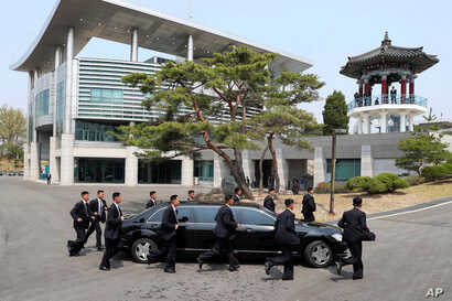 North Korean security persons run by a car carrying North Korean leader Kim Jong Un return to the North side for a lunch break after a morning session of a summit meeting with South Korean President Moon Jae-in at the border village of Panmunjom in D...