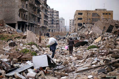 People walk amid the rubble as they carry belongings that they collected from their houses in the government controlled area of Aleppo, Syria, Dec. 17, 2016.