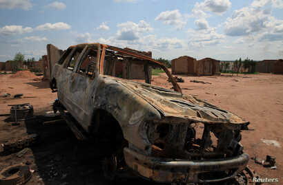 A burnt-out car is seen in Kapende, a Congolese neighborhood of Lucapa, Angola, Oct. 19, 2018.