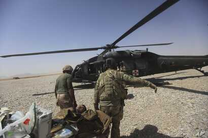 "FILE - A U.S. Army medics carry a wounded soldier in Afghanistan's Helmand province  Sept. 6, 2011. Two U.S. soldiers were killed and two wounded when the came under enemy fire while on a ""train, advise and assist mission"" in Kunduz district, norther..."