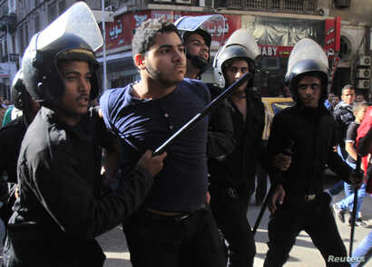 Riot police detain a man who was taking part in a protest against a new law in Egypt that restricts demonstrations, in downtown Cairo, Nov. 26, 2013.