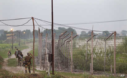 Indian Border Security Force soldiers walk near the India-Pakistan international border area at Gakhrial boder post in Akhnoor sector, about 48 kilometers (30 miles) from Jammu, India, Oct. 1, 2016.