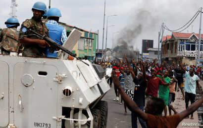 Residents chant slogans against Congolese President Joseph Kabila as UN peacekeepers patrol during demonstrations in the streets of the Democratic Republic of Congo's capital Kinshasa, December 20, 2016.