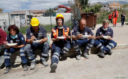 Rescuers rest and have food following an earthquake in Amatrice, central Italy, Aug. 25, 2016.