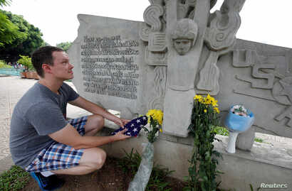 English teacher Derek Davis from the U.S. places a U.S. flag and flowers in memory of the late U.S. Senator John McCain (R-Az.) at the McCain Memorial in Hanoi, Vietnam, Aug. 26, 2018.