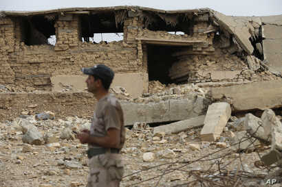 An Iraqi soldier stands in front a damaged part of the ancient site of Nimrud, which was destroyed by Islamic State militants, some 19 miles (30 kilometers) southeast of Mosul, Iraq, Nov. 16, 2016.
