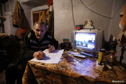A man fills out registration papers before casting his vote in a mobile ballot box during voting in a referendum in the village of Pionerskoye outside Simferopol March 16, 2014.  Crimeans decided on Sunday whether to break away from Ukraine and join