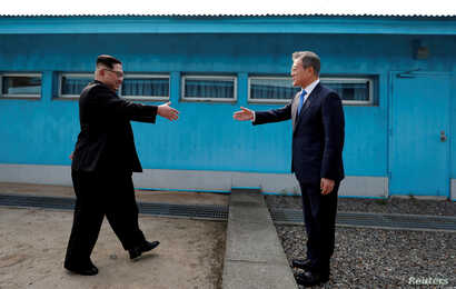 FILE - South Korean President Moon Jae-in and North Korean leader Kim Jong Un, left, are about to shake hands on their first meeting at the truce village of Panmunjom inside the demilitarized zone separating the two Koreas, South Korea, April 27, 201...