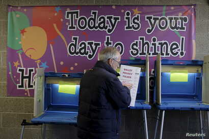 A voter casts his ballot in the Wisconsin presidential primary election at a voting station in Milwaukee, Wisconsin, United States, April 5, 2016.