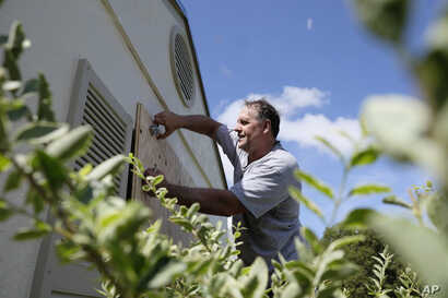 With Hurricane Irma threatening to march through Florida, Ben Tozour installs wood shutters on his home in the Cutler Bay section of Miami, Sept. 8, 2017.