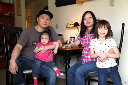 FILE - Korean adoptee Adam Crapser poses with daughters, Christal and Christina, and his wife, Anh Nguyen, in the family's living room in Vancouver, Washington, March 19, 2015. Crapser, who was adopted as a 3-year-old from South Korea almost four dec...