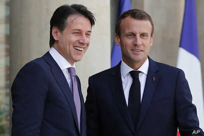 French president Emmanuel Macron, right, welcomes Italian Premier Giuseppe Conte before their meeting at the Elysee Palace in Paris, June 15, 2018. The two meet amid tensions between the two countries over migration.