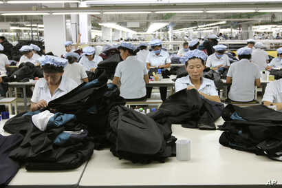 FILE - North Korean workers assemble Western-style suits at the South Korean-run ShinWon Corp. garment factory inside the Kaesong industrial complex in Kaesong, North Korea.