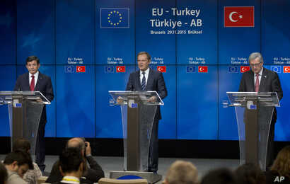 Turkish Prime Minister Ahmet Davutoglu (L), European Council President Donald Tusk (C) and European Commission President Jean-Claude Juncker address a media conference at an EU-Turkey summit in Brussels, Nov. 29, 2015.