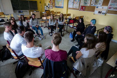 Laura Schulmann, center right, and Sophie Steiert, center left, listen to questions from students about Jewish daily life in Germany during a lesson as part of a project about religions at the Bohnstedt Gymnasium high school in Luckau, Germany, June ...