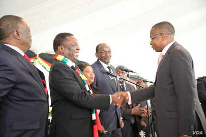 President Mnangagwa (right) talks to Zimbabwe's new Finance Minister Mthuli Ncube at the State House in Harare, Sept. 10, 2018.