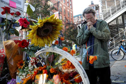 FILE - A man prays after laying flowers at a roadside memorial to the victims of the Oct. 31 attack alongside a bike path at Chambers Street in New York City, Nov. 2, 2017.