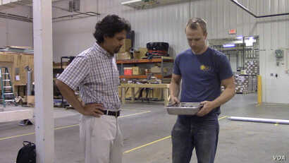 Notre Dame engineering professor Yahya Kurama (left) and graduate student Michael Brandes look over a container of aggregate.