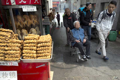 In this Wednesday, April 13, 2016 photo, shoppers past by traditional food on sale in Beijing. China's economic growth slowed in the first quarter to 6.7 percent compared with the previous year, according to official data released on April 15, 2016.