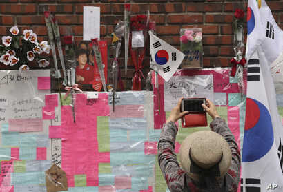 A supporter of former South Korean President Park Geun-hye takes photo with smartphone in front of the wall of Park's private home in Seoul, March 27, 2017.