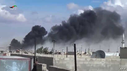 Smoke billows from buildings in the central Syrian town of Talbisseh in Homs province. Russian warplanes carried out airstrikes in three Syrian provinces, including Homs, along with regime aircraft, according to a Syrian security source, Sept. 30, 20...