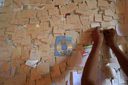 A shopper ties a message note for the victims of the crashed Malaysia Airlines Flight 17, at a shopping mall in Petaling Jaya, near Kuala Lumpur, Malaysia, Thursday, July 24, 2014. At least 51 containers holding bodies and body parts of victims of th