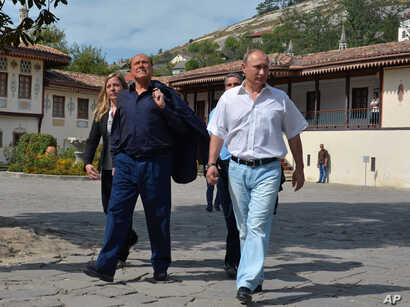 Russian President Vladimir Putin, right, and former Italian Prime Minister Silvio Berlusconi visit the Khan's Palace in the town of Bakhchisarai, Crimea, Saturday, Sept. 12, 2015.