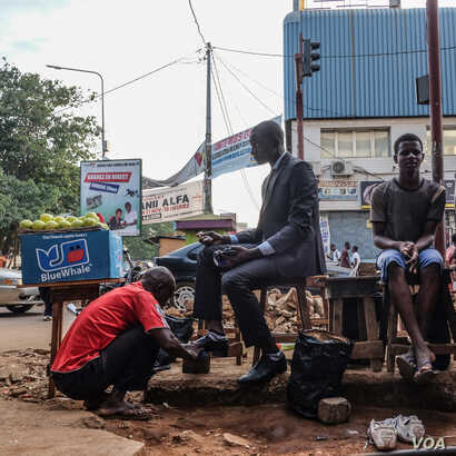 Ricci Shryock: An accountant gets his shoes shined on his way to work in Conakry, Guinea.