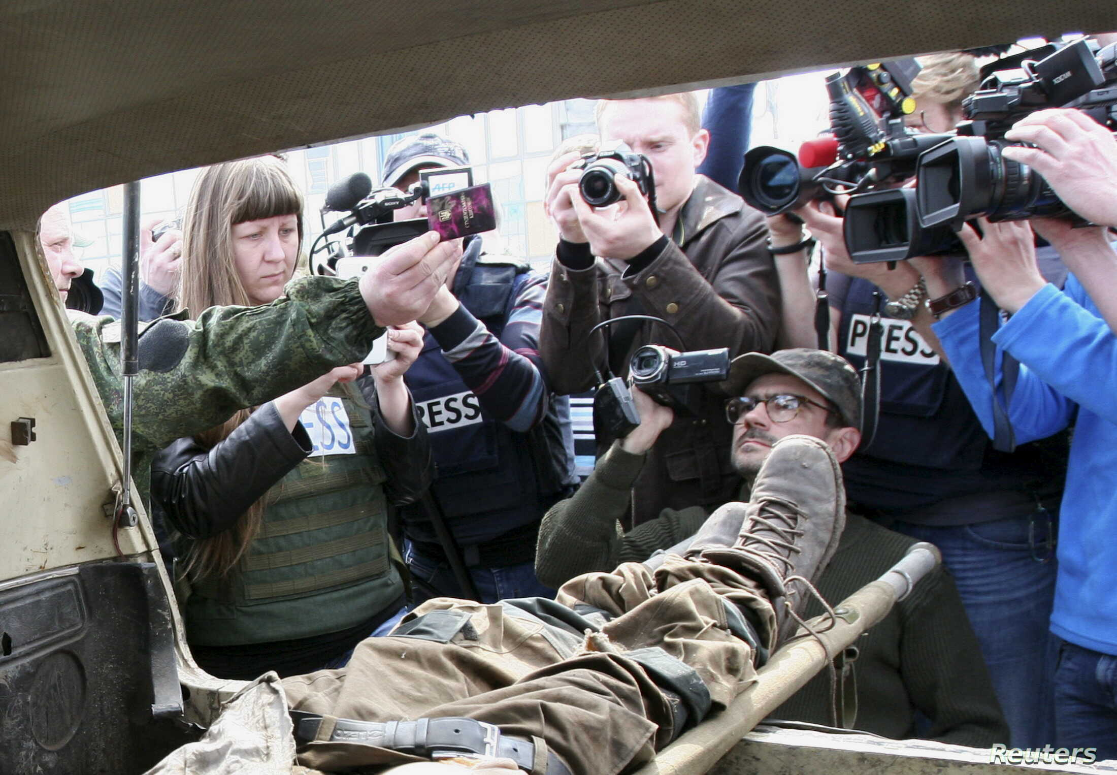 Journalists take photos and video of the body of a man, a Ukrainian serviceman according to separatist self-proclaimed Donetsk People's Republic (DNR) officials, in Donetsk, April 13, 2015.