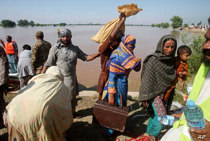 Pakistani villagers, who have been effected by the flood, arrive to find safe shelters in Pindi Bhatian, 105 kilometers (65 miles) northeast of Lahore, Pakistan, Sept. 8, 2014.