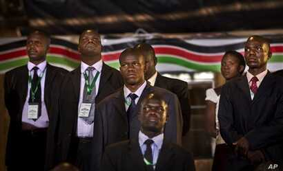 Security and bodyguards of the election commission chairman stand as he delivers a statement to the media, at the National Election Center